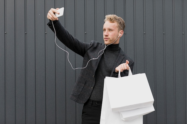 Homme blond en noir prenant un selfie avec smartphone