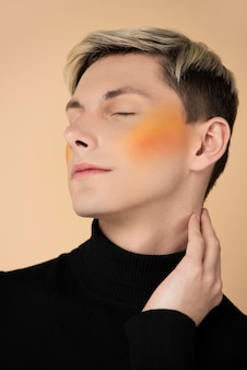 Homme blond portant du blush orange
