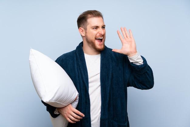 Homme blond en pyjama criant avec la bouche grande ouverte