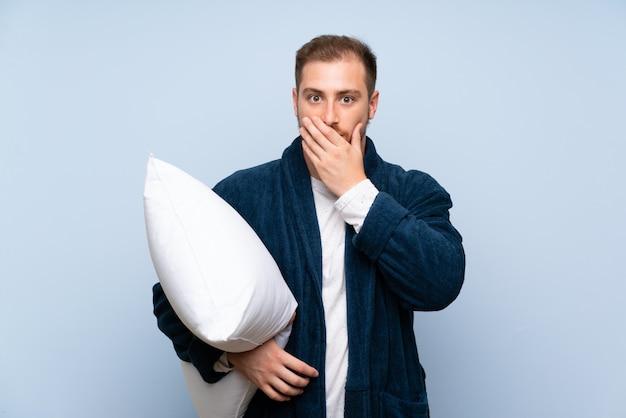 Homme blond en pyjama sur un mur bleu avec une expression faciale surprise