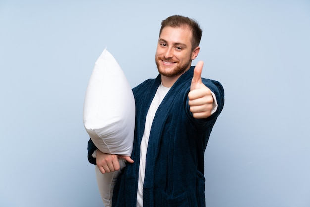 Un homme blond en pyjama sur un mur bleu avec le pouce levé parce qu'il s'est passé quelque chose de bien