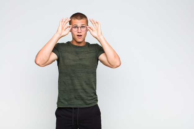 Homme blond se sentant choqué, étonné et surpris, tenant des lunettes avec un regard étonné et incrédule