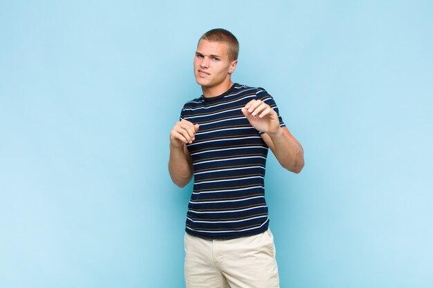 Homme blond se sentant dégoûté et nauséeux, s'éloignant de quelque chose de méchant, malodorant ou puant