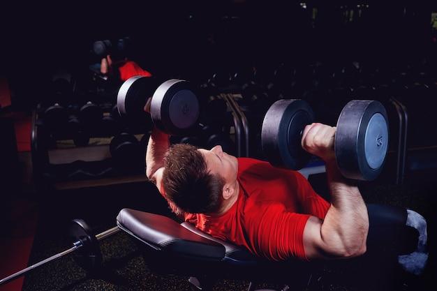 Un homme blond sportif faisant des exercices avec des haltères dans la salle de sport