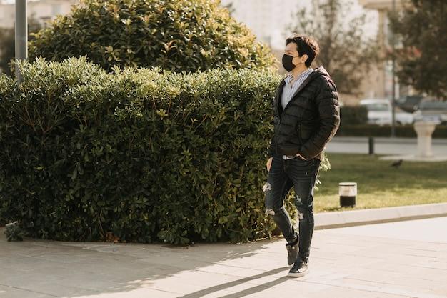 Homme en blouson de cuir noir et masque noir marchant dans le parc. photo de haute qualité