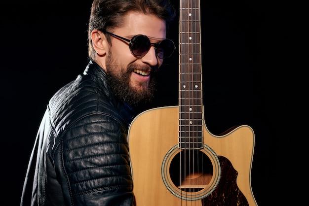 Homme en blouson de cuir noir tenant le style de vie des célébrités de la musique de guitare