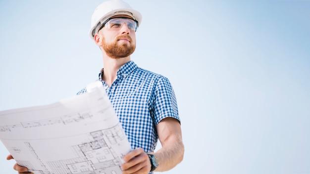 Homme avec blueprint en détournant les yeux