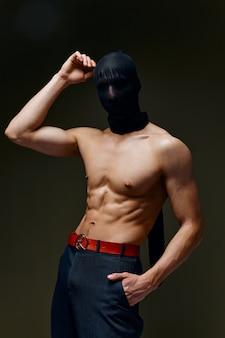 L'homme avec le bodybuilder de gâteau de muscles pompés presse le pantalon et le masque de fond gris