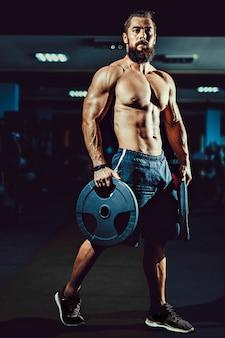Homme bodybuilder musculaire athlète posant avec des haltères dans la salle de gym.