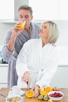 Homme, boire, jus orange, et, femme, couper, fruits, dans, cuisine