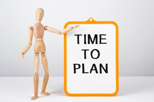 Homme en bois montre avec une main au tableau blanc avec texte temps de planifier, concept