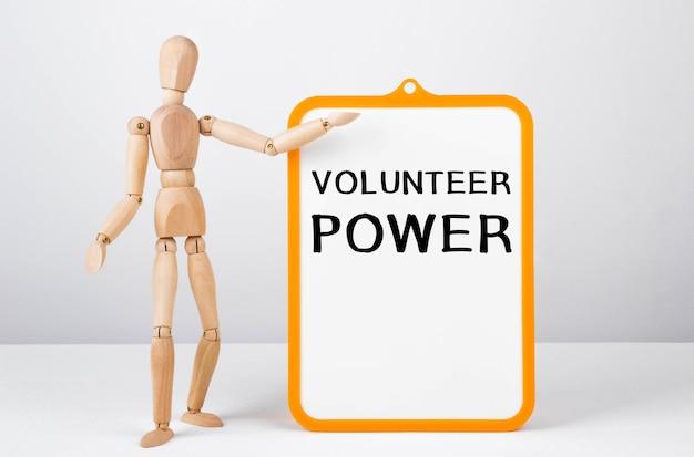 Homme en bois montre avec une main au tableau blanc avec texte volunteer power.