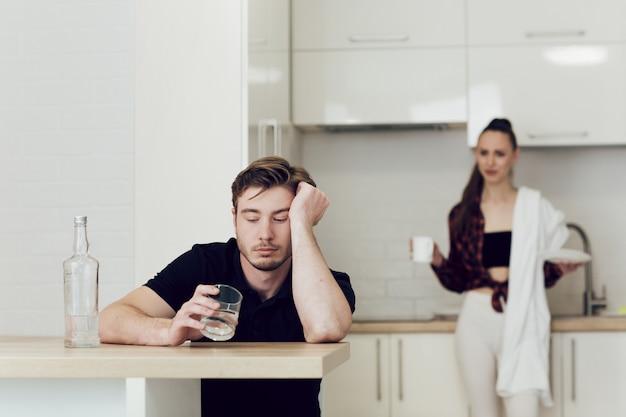 Un homme boit assis à une table dans la cuisine, une femme derrière lui se querelle et crie.
