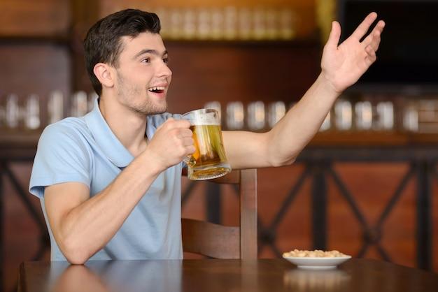 L'homme boit de la bière au bar et fait appel au serveur.