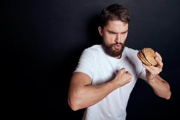 Un homme boit de la bière dans un verre et mange de la malbouffe de la restauration rapide frite