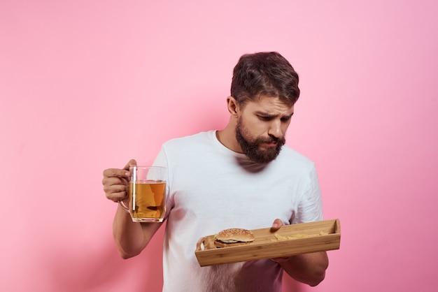 Un homme boit de la bière dans un verre et mange de la malbouffe