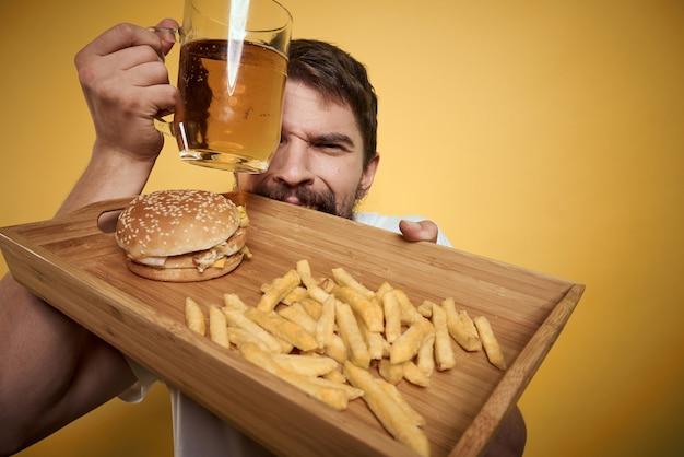 L'homme boit de la bière dans un verre et mange de la restauration rapide frite