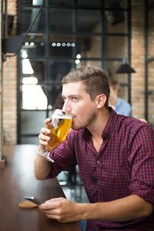 L'homme boit de la bière et utilise un téléphone intelligent dans le pub