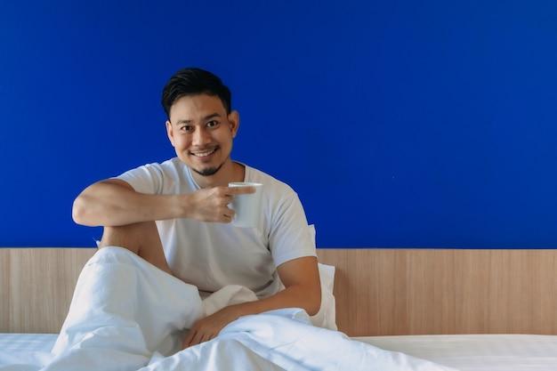 L'homme boit du café du matin sur le lit avec un fond d'écran bleu