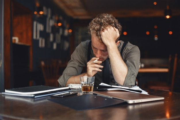L'homme boit du whisky. homme d'affaires lit des documents. réalisateur en chemise et bretelles.
