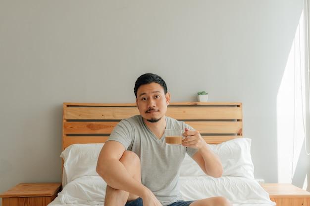 L'homme boit une tasse de café sur le lit dans sa chambre.