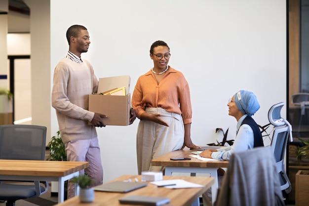 Un homme avec une boîte d'effets personnels est présenté à ses collègues à son nouveau travail
