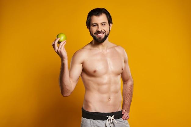 Homme en bonne santé avec un torse nu est titulaire de pomme.