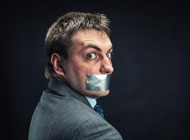 Homme avec la bouche couverte de ruban adhésif
