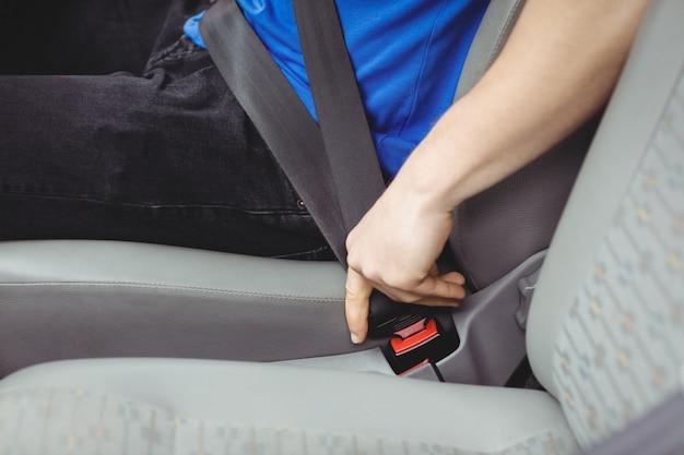 Homme bouclant sa ceinture de sécurité dans une camionnette