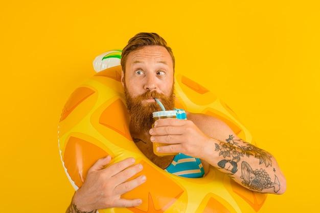 L'homme avec la bouée de sauvetage de l'enfant boit un jus de fruit