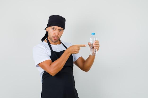 Homme de boulanger pointant sur une bouteille d'eau en t-shirt
