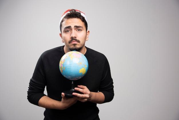 Homme bouleversé au chapeau du père noël posant avec un globe.