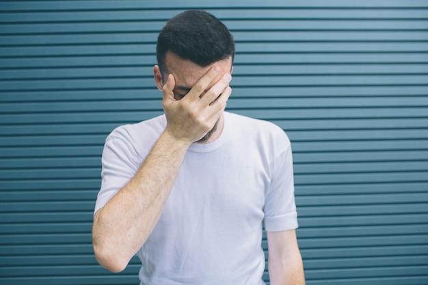 Homme bouleversé est debout et couvre le visage avec la main. il est malheureux. guy a honte. isolé sur rayé