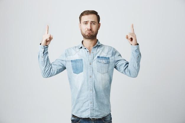 Homme bouleversé et sombre pointant les doigts vers le haut, faisant la moue