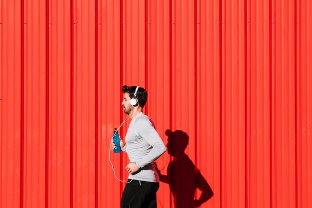 Homme avec une bouteille qui coule près du mur rouge