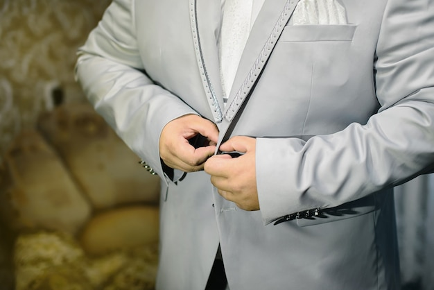 Un homme boutonne une veste grise dans un style rétro