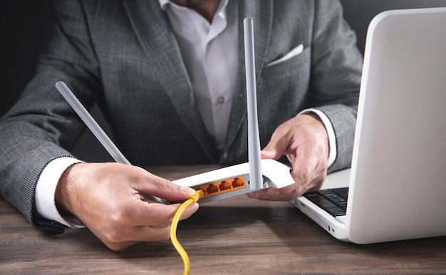 Homme branchant le câble internet dans le routeur wifi.