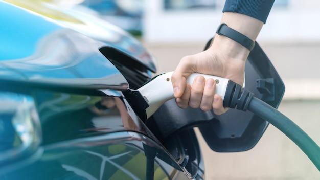 Homme branchant le chargeur dans une voiture électrique à la station de charge