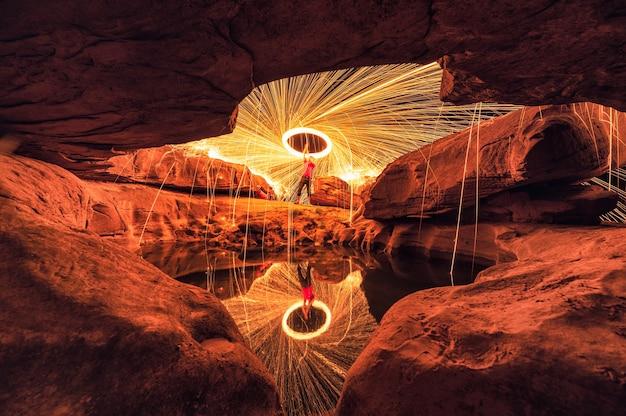 Homme brandissant un tourbillon de feu d'étincelle dans la grotte de trou de pierre et la réflexion de l'étang dans la nuit à sam phan bok, ubon ratchathani