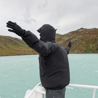 Homme, à, bras tendu, sur, bateau, à, lac pehoe, parc national torres del paine, patagonie, chili