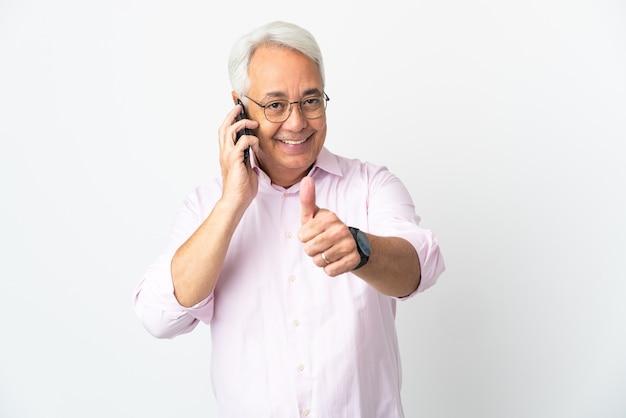 Homme brésilien d'âge moyen isolé sur fond blanc en gardant une conversation avec le mobile tout en faisant les pouces vers le haut
