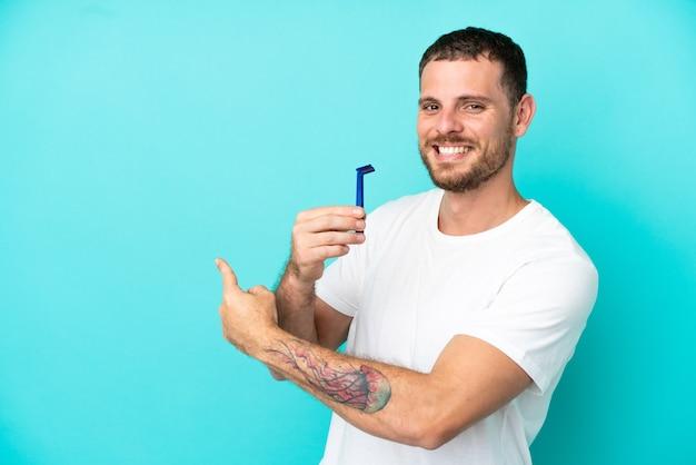 Homme brésilien rasant sa barbe isolé sur fond bleu pointant vers l'arrière