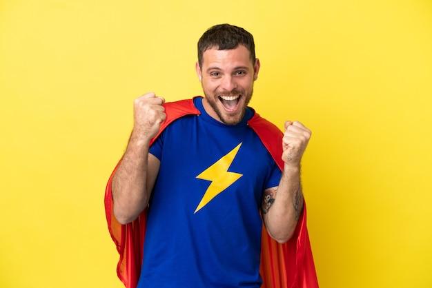 Homme brésilien de super héros isolé sur fond jaune célébrant une victoire en position de vainqueur