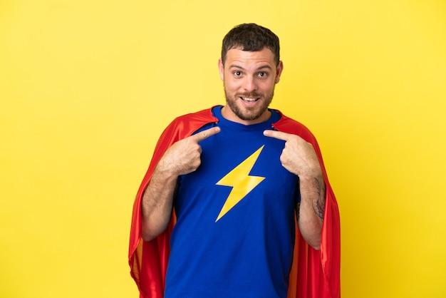 Homme brésilien de super héros isolé sur fond jaune avec une expression faciale surprise