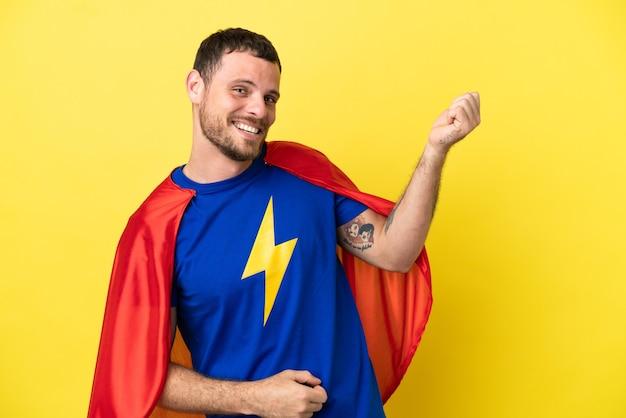 Homme brésilien de super héros isolé sur fond jaune faisant un geste de guitare