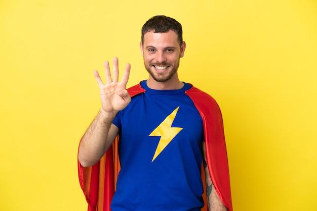 Homme brésilien de super héros isolé sur fond jaune heureux et comptant quatre avec les doigts