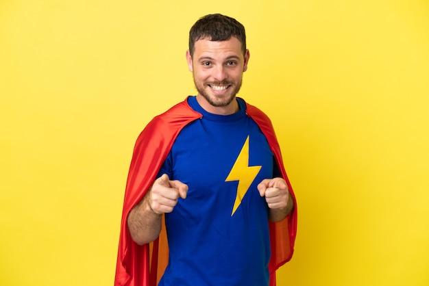 Homme brésilien de super héros isolé sur fond jaune pointant vers l'avant et souriant