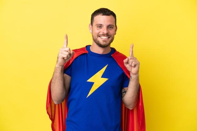 Homme brésilien de super héros isolé sur fond jaune pointant vers une excellente idée