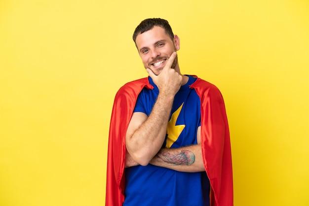 Homme brésilien de super héros isolé sur fond jaune souriant