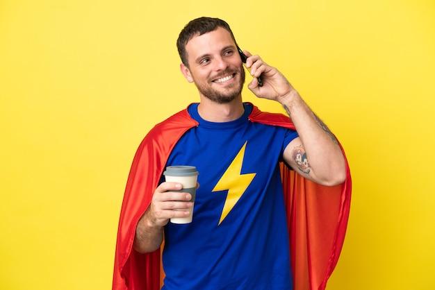 Homme brésilien de super héros isolé sur fond jaune tenant du café à emporter et un mobile